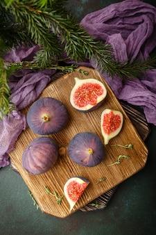 Frutas suculentas de figo inteiro e um figo cortado em uma tábua de madeira. vista do topo