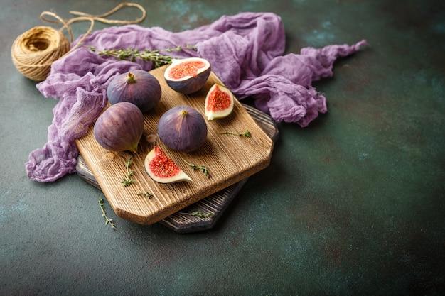 Frutas suculentas de figo inteiro e um figo cortado em uma tábua de madeira