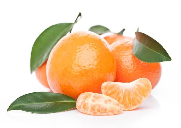 Frutas tangerinas orgânicas frescas de tangerinas com folhas com metades descascadas em fundo branco