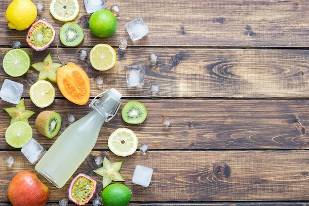 Frutas tropicais com gelo e uma garrafa de refrigerante