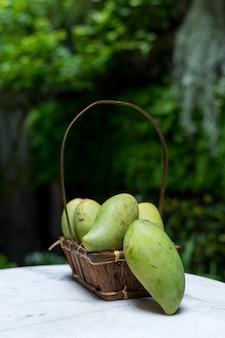 Frutas tropicais de manga na cesta de madeira