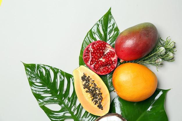 Frutas tropicais e folhas na superfície branca