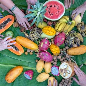 Frutas tropicais em folhas de bananeira verdes e mãos de pessoas. grupo de amigos felizes, tendo uma boa comida, curtindo a festa e a comunicação. manga, mamão, pitahaya, banana, melancia, abacaxi e mãos