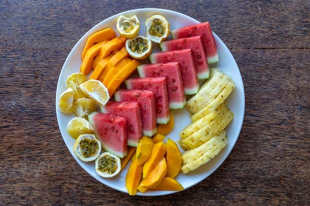 Frutas tropicais em um prato de café da manhã, close-up, vista superior. melancia fresca, maracujá, abacaxi, manga, mamão, laranja para comer em restaurante de praia, ilha de zanzibar, tanzânia, áfrica