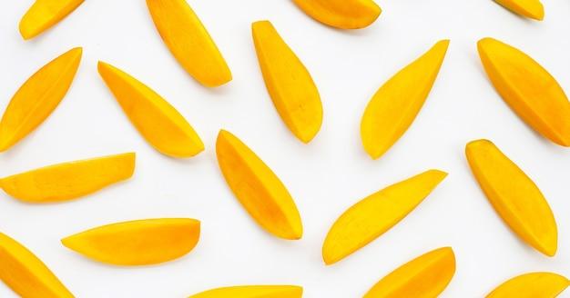 Frutas tropicais, fatias de manga na superfície branca.