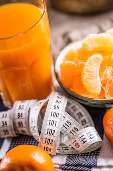 Frutas tropicais frescas e fita métrica tangerinas descascadas e fatias de tangerina em uma mesa