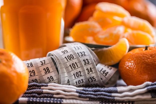 Frutas tropicais frescas e fita métrica. tangerinas, tangerina descascada e fatias de tangerina em um pano azul. suco de mandarine.