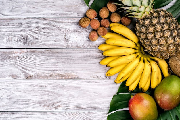 Frutas tropicais frescas na vista superior de madeira. banana, abacaxi, coco, manga, lichia, castanhas.