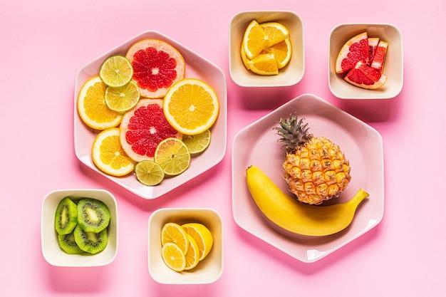 Frutas tropicais inteiras e fatias em pratos, vista superior.
