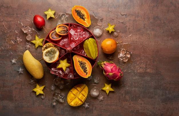Frutas tropicais mamão, fruta do dragão, rambutan, tamarindo, granadilha, carambola, manga com cubos de gelo em um fundo escuro.