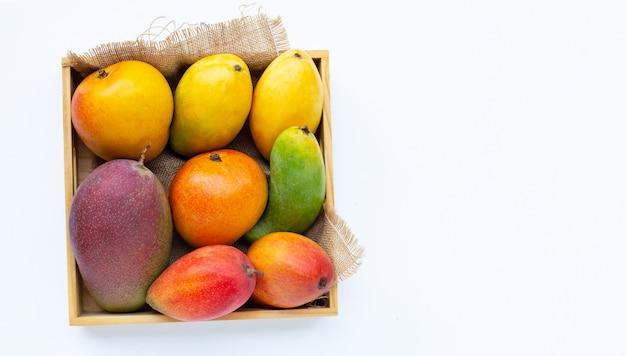 Frutas tropicais, manga em caixa de madeira no fundo branco.