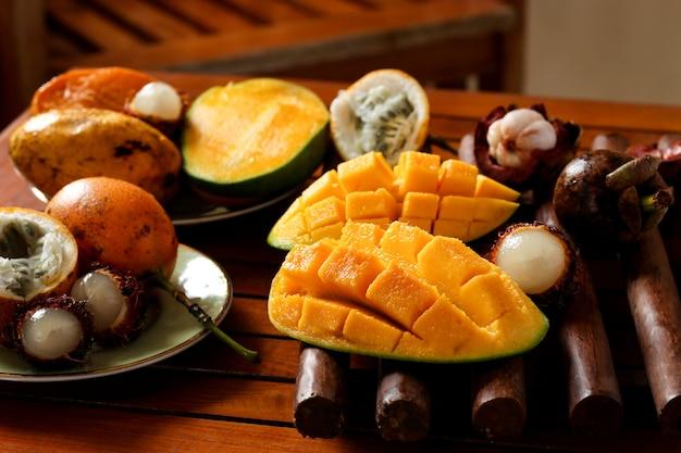 Frutas tropicais: maracujá, rambutan, mangostão e manga estão localizados em uma mesa de madeira