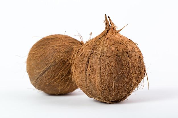 Frutas tropicais marrons deliciosos maduros suculentos cocos isolados em uma mesa branca