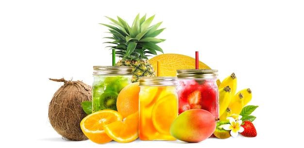 Frutas tropicais variadas com suco fresco em potes de pedreiro isolados em um branco