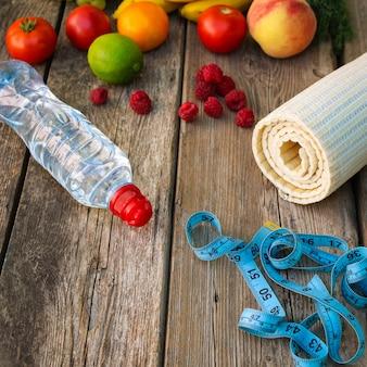 Frutas, vegetais, água, fita métrica e artigos esportivos