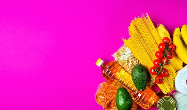 Frutas, vegetais, cereais, papel higiênico em uma superfície rosa