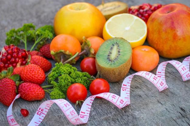 Frutas, vegetais e fita métrica na dieta