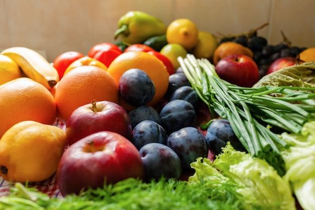 Frutas, vegetais e verduras estão sobre a mesa, luz natural da janela.