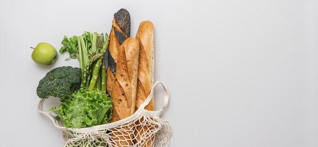 Frutas, vegetais verdes e baguete de pão em uma bolsa de malha em fundo branco, vista superior