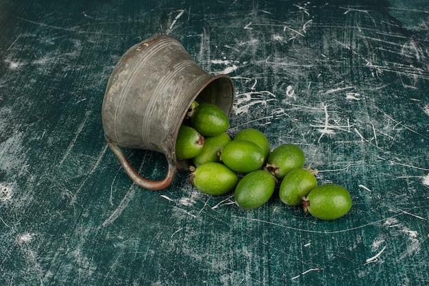 Frutas verdes feijoa caindo do vaso na superfície de mármore.