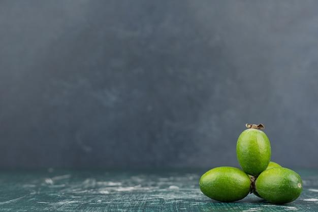Frutas verdes feijoa em superfície de mármore.