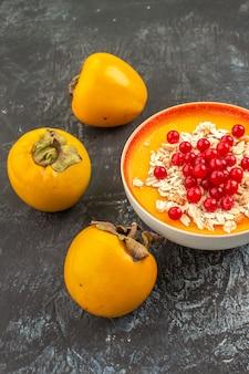 Frutas vermelhas tigela de frutas vermelhas três caquis apetitosos