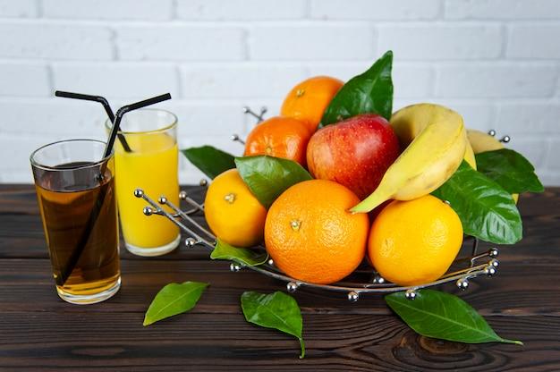 Fruteira com frutas e dois copos de suco