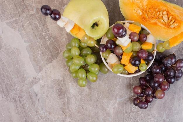 Fruteira e frutas frescas na superfície de mármore.