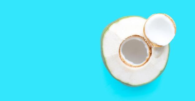 Fruto de coco jovem verde fresco sobre fundo azul.