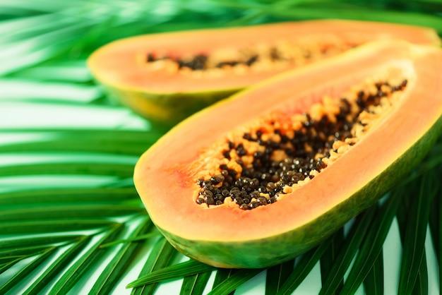 Fruto exótico da papaia sobre as folhas de palmeira verdes tropicais. pop art design, conceito criativo de verão. comida vegetariana crua.