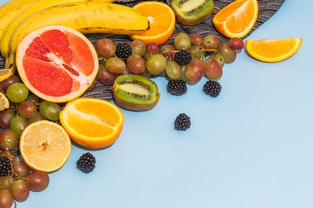 Frutos cítricos cortados ao meio; uvas; banana; kiwi em fundo azul