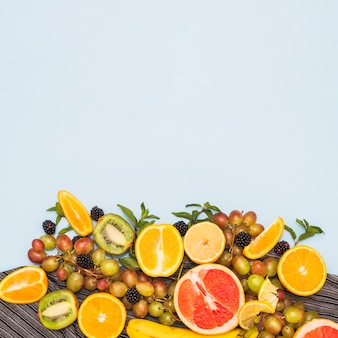 Frutos cortados ao meio; uvas e amoras contra o pano de fundo azul