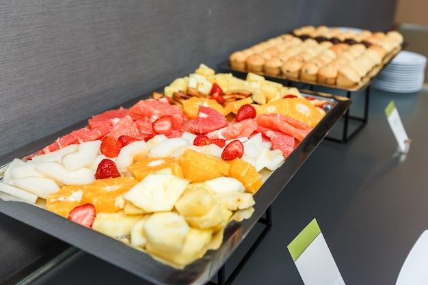 Frutos cortados e queques doces em uma tabela servida em uma ruptura de café no escritório.