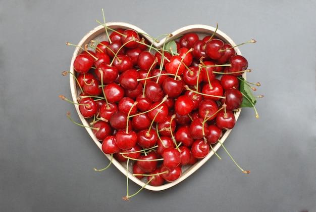 Frutos da cereja do verão na caixa dada forma coração.
