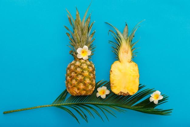 Frutos de abacaxi de verão tropical inteiro de abacaxi e metades de abacaxi fatiado com composição de flores de plumeria tropical sobre fundo de verão de cor azul. postura plana. banco de fotos de alta qualidade