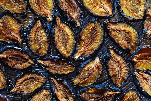 Frutos de ameixas secas espalhados na vista superior do secador. plano de fundo de alimentos saudáveis