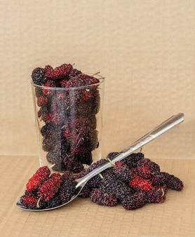 Frutos de amoreira orgânicos com colher de aço inoxidável