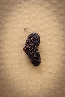 Frutos de amoreira orgânicos em fundo de papelão