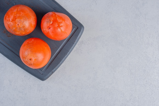 Frutos de caqui de laranja madura. caqui fresco na placa de madeira.