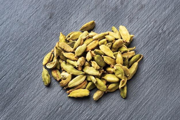 Frutos de cardamomo inteiro seco em uma mesa de concreta preta. especiaria indiana picante.