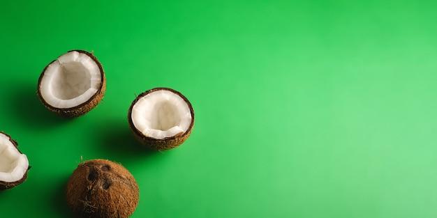 Frutos de coco em fundo verde simples, banner com espaço de cópia