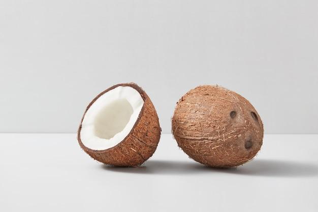 Frutos de coco maduros exóticos naturais com um inteiro e metade da noz em um fundo cinza claro duotônico com sombras suaves, copie o espaço. conceito vegano.