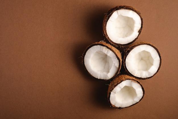 Frutos de coco no fundo liso marrom, conceito tropical de comida abstrata, espaço de cópia de vista superior