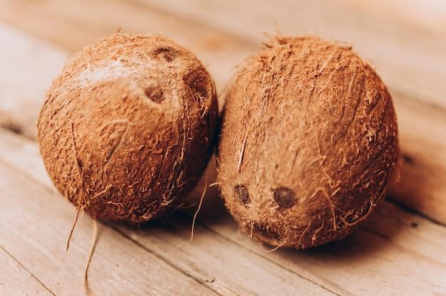 Frutos de coco tropical em um fundo de madeira em estilo rústico.
