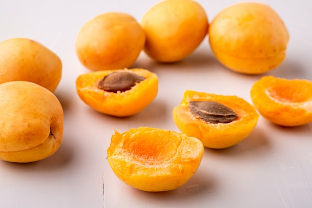 Frutos de damasco cortados na parede branca