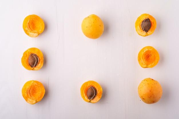 Frutos de damasco fatiados em superfície branca
