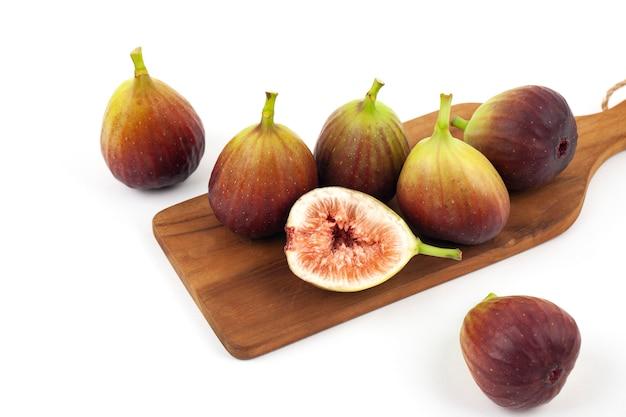Frutos de figo e um corte figos na tábua de madeira