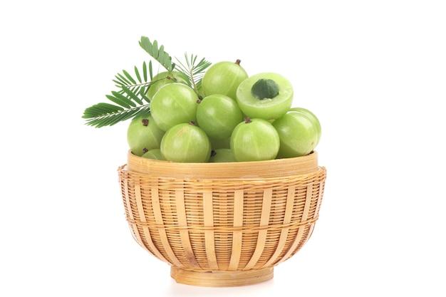 Frutos de groselha indiana ou phyllanthus emblica e folhas verdes, isoladas no fundo branco.