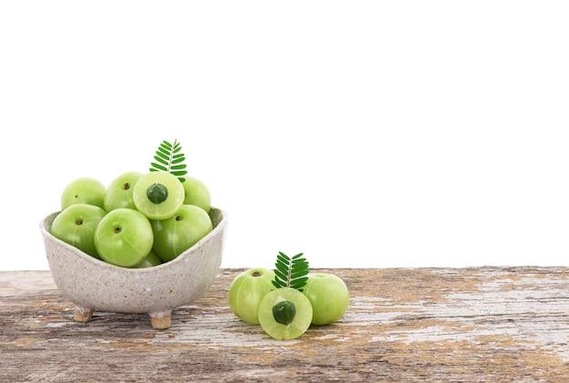 Frutos de groselha indiana ou phyllanthus emblica em uma tigela sobre a mesa de madeira com traçado de recorte.