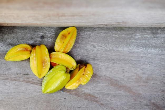 Frutos de maçãs estrela amarela no assoalho de madeira